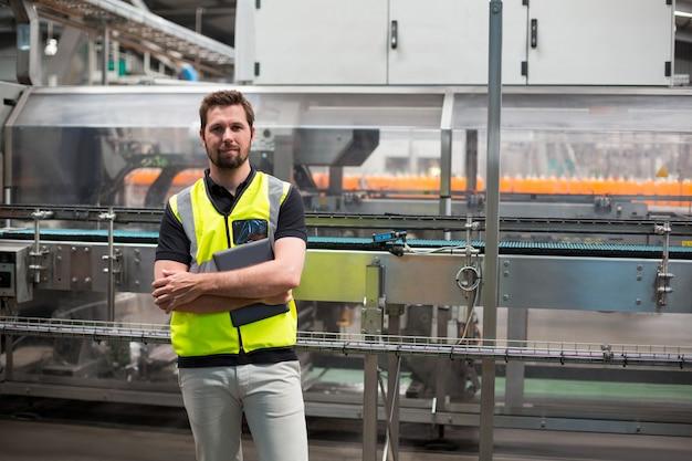 Porträt des selbstbewussten fabrikarbeiters, der mit einem digitalen tablett steht
