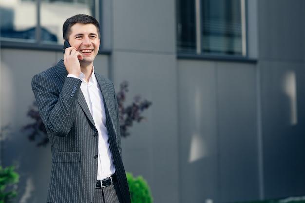 Porträt des selbstbewussten geschäftsmannes im klassischen anzug, der auf smartphone spricht und in straße geht. junger geschäftsmann, der geschäftsgespräch hat