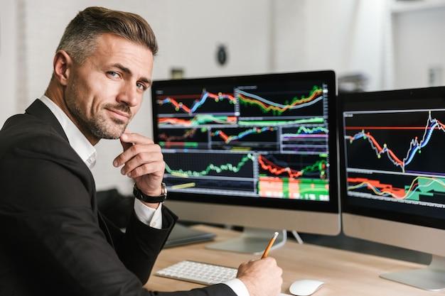 Porträt des selbstbewussten geschäftsmanns der 30er jahre, der anzug trägt, der im büro sitzt und mit digitaler grafik am computer arbeitet