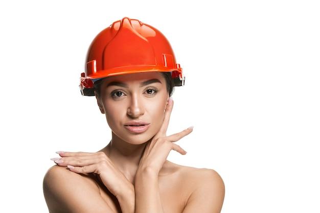 Porträt des selbstbewussten glücklichen lächelnden arbeiters der frau im orangefarbenen helm