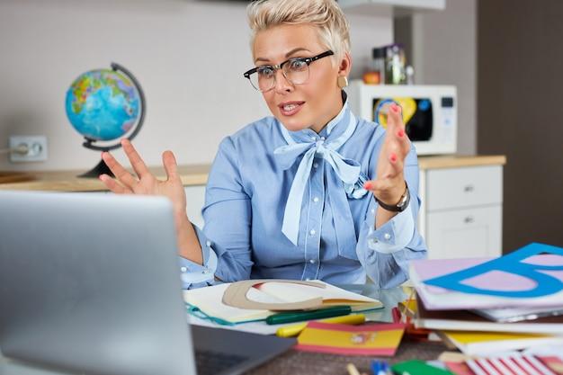 Porträt des selbstbewussten gut aussehenden lehrers, der am tisch sitzt