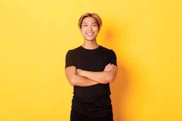 Porträt des selbstbewussten gutaussehenden asiatischen mannes, der zufrieden lächelt und über gelber wand in der schwarzen kleidung steht.