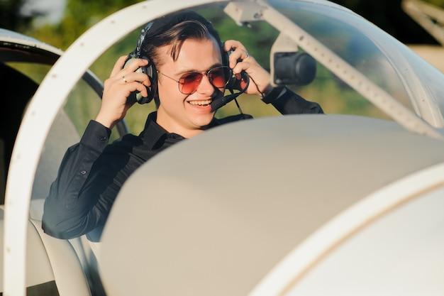 Porträt des selbstbewussten jungen mannpiloten im kleinen flugzeug