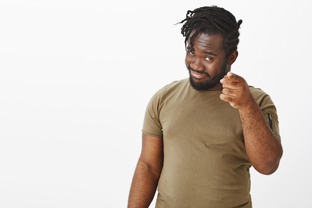 Porträt des selbstbewussten kerls in einem braunen t-shirt, das gegen die weiße wand aufwirft