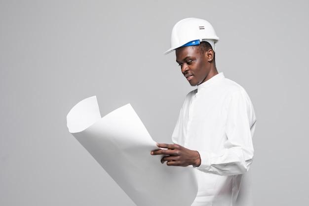 Porträt des selbstbewussten, lächelnden afroamerikanischen architektenmannes mit blaupause, die kamera lokalisiert auf grauem hintergrund betrachtet