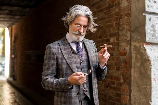 Porträt des selbstbewussten mannes, der zigarre hält