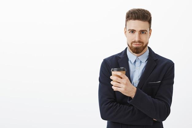 Porträt des selbstbewussten und erfolgreichen gutaussehenden geschäftsmannes im eleganten anzug, der pappbecher kaffee grinst, der vor freude grinst, befehl mag und geschäft unter kontrolle gegen weiße wand nimmt