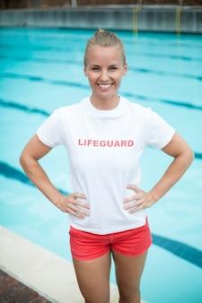 Porträt des selbstbewussten weiblichen rettungsschwimmers, der am pool steht