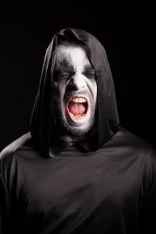 Porträt des sensenmanns, der über schwarzem hintergrund schreit. halloweenkostüm.
