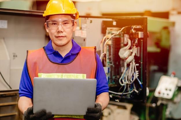 Porträt des servicetechnikerteams, das mit elektronischer drahtrückwand der schwerindustriemaschine für wartungsreparatur arbeitet und mit laptop-computer für analyseprobleme repariert.