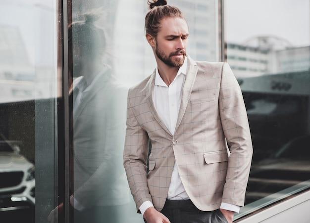 Porträt des sexy gutaussehenden mannes kleidete im eleganten beige karierten anzug an