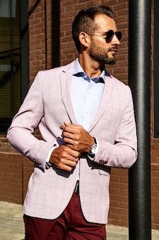 Porträt des sexy gutaussehenden modegeschäftsmannmodells gekleidet im eleganten anzug, der nahe ziegelmauer auf dem straßenhintergrund aufwirft. metrosexuell