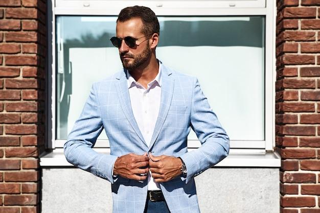 Porträt des sexy gutaussehenden modegeschäftsmannmodells, gekleidet im eleganten blauen anzug, der auf straßenhintergrund aufwirft. metrosexuell