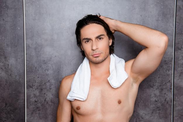 Porträt des sexy jungen mannes mit weißem handtuch, das sein schwarzes haar berührt