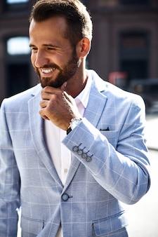 Porträt des sexy lächelnden gutaussehenden modegeschäftsmannmodells, gekleidet im eleganten blauen anzug, der auf straßenhintergrund aufwirft. metrosexuell