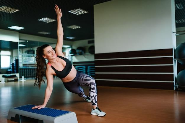 Porträt des sexy muskulösen mädchens, das sportbekleidung trägt, die übungen auf der stufenplattform, aerobic im fitnessstudio tut