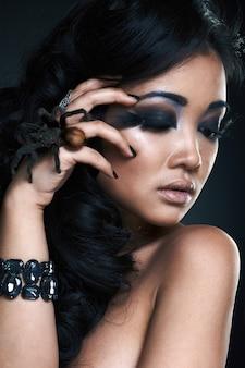 Porträt des sexy schönen jungen asiatischen modells mit spinne