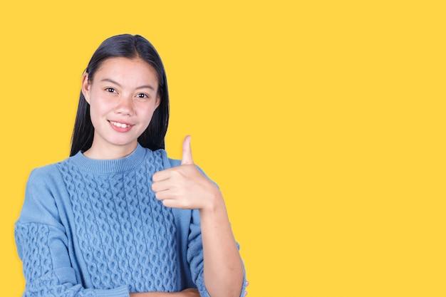 Porträt des showdaumens der jungen frau oben lokalisiert auf gelbem hintergrund