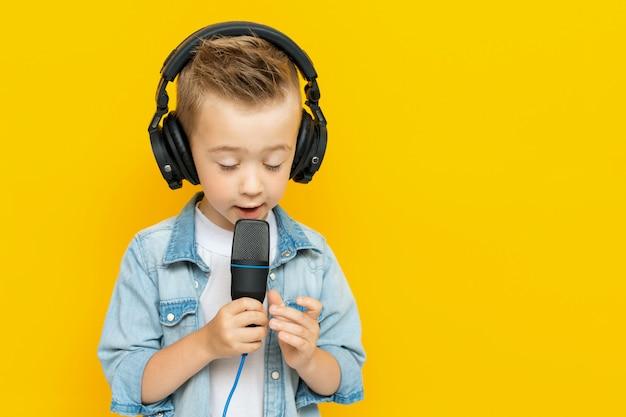 Porträt des singenden kleinen jungen mit kopfhörern und mikrofon