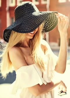 Porträt des sinnlichen blonden frauenmodells gekleidet im weißen kleid und im sommerstrandhut, der auf dem straßenhintergrund hinter sonnenuntergang aufwirft