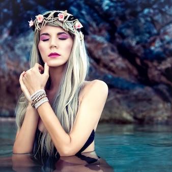 Porträt des sinnlichen blonden mädchens in einem kranz im meer