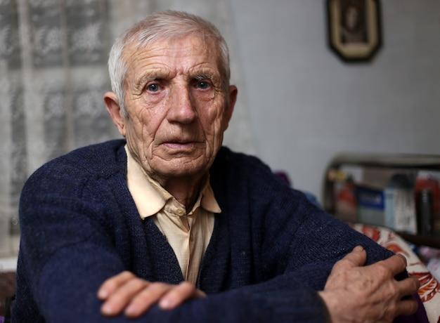 Porträt des sitzenden älteren mannes zu hause