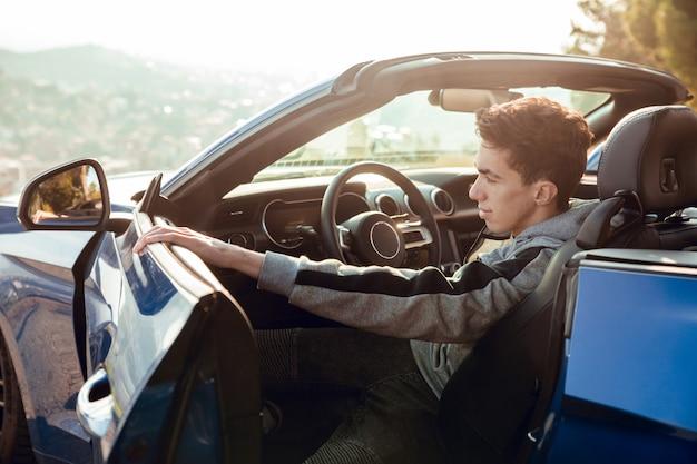 Porträt des sitzenden jungen in der luxussportautoöffnungstür bei sonnenaufgang