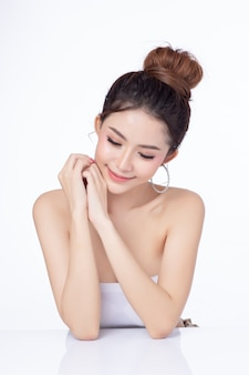 Porträt des sitzenden lächelns der attraktiven asiatischen frau auf weißem hintergrund.
