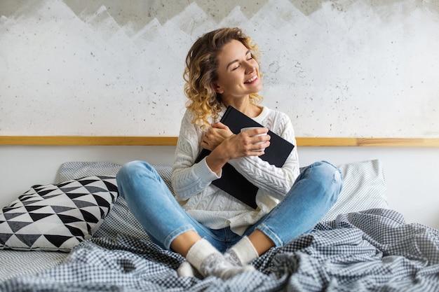 Porträt des sitzens attraktiver frau mit lockigem blondem haar auf bett, buch und kaffee in der tasse haltend