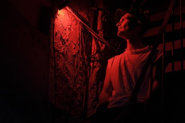 Porträt des sitzens auf dem erwachsenen mann der treppe mit farbigem rotem licht und dunklem hintergrund.