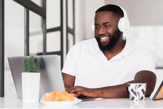 Porträt des smiley-mannes, der arbeit von zu hause aus genießt