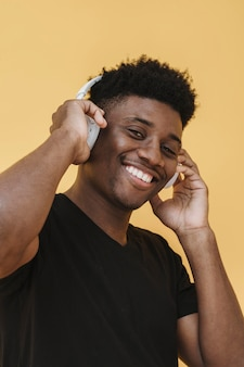 Porträt des smiley-mannes, der musik auf kopfhörern hört