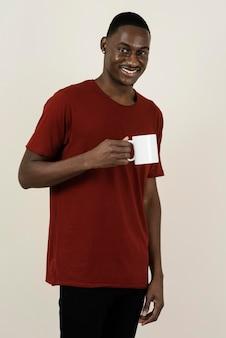 Porträt des smiley-mannes in einem t-shirt, das becher hält