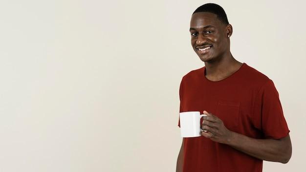 Porträt des smiley-mannes in einem t-shirt, der becher mit kopienraum hält