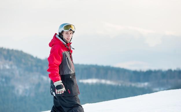 Porträt des snowboarders stehend auf einen berg