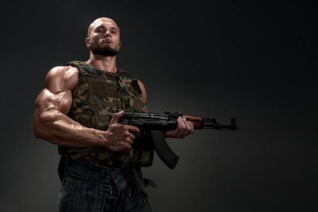 Porträt des soldaten mit einer waffe auf schwarzem hintergrund