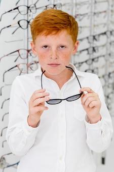 Porträt des sommersprossejungen kamera beim halten von brillen betrachtend