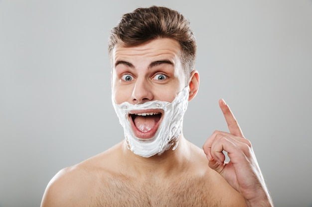 Porträt des spielerischen kerls mit dem dunklen kurzen haar, das spaß beim rasieren des gesichtes lokalisiert über grauer wand hat
