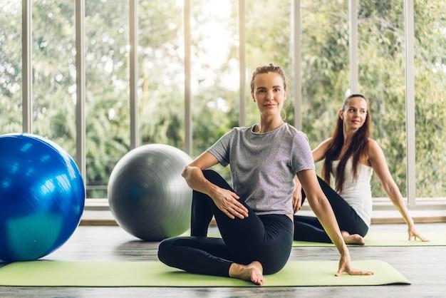 Porträt des sport attraktiven menschen frau in sportbekleidung sitzen entspannen und yoga-fitness-übung mit blauem fitball im klassentraining im sportclub üben