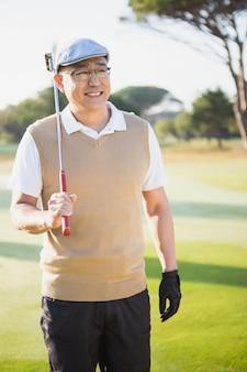 Porträt des sportlers, der seinen golfschläger hält und wegschaut