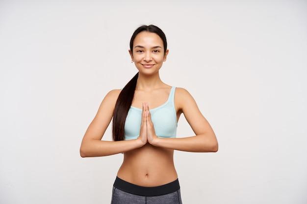 Porträt des sportlichen, erwachsenen asiatischen mädchens mit dem dunklen langen haar. tragen sie sportkleidung und meditieren sie, haben sie ein friedliches lächeln. falten sie die hände im namaste-zeichen. beobachten in die kamera isoliert auf weißem hintergrund