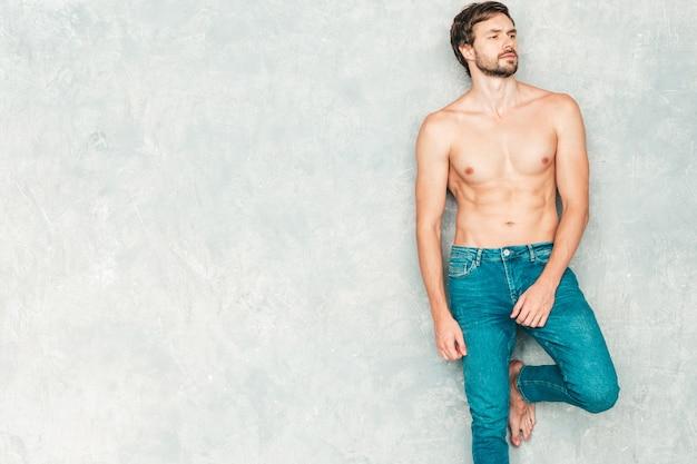 Porträt des sportlichen, gutaussehenden starken mannes. gesundes lächelndes athletisches eignungsmodell, das nahe grauer wand in den jeans aufwirft. Kostenlose Fotos