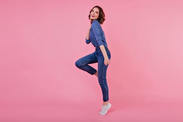 Porträt des sportlichen mädchens in voller länge mit gewelltem haar. innenaufnahme der springenden jungen frau in den jeans und im blauen hemd.