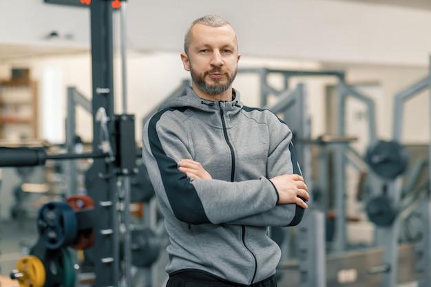Porträt des sportlichen mannes mit den gefalteten händen in der turnhalle