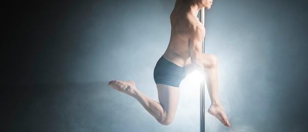 Porträt des starken männlichen modells, das einen stangentanz durchführt