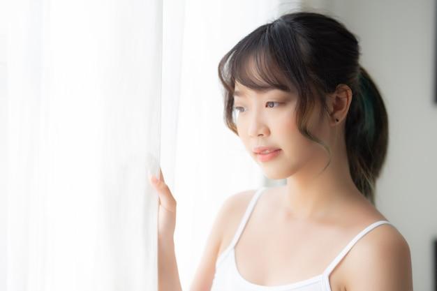Porträt des stehenden blickes der schönen jungen asiatischen frau am fenster