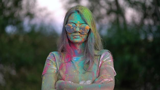 Porträt des stehenden jungen, der beim holi-festival mit farbigem pulver bedeckt wird.