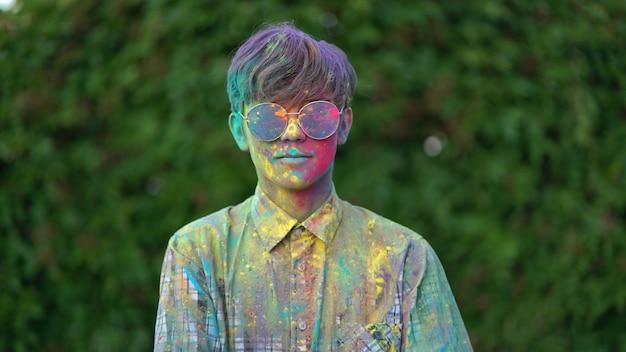 Porträt des stehenden jungen, der mit farbigem pulver bedeckt wird