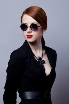 Porträt des stil-rothaarigen mädchens in den schwarzen kleidern auf grau