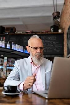 Porträt des stilvollen älteren mannes, der arbeitet